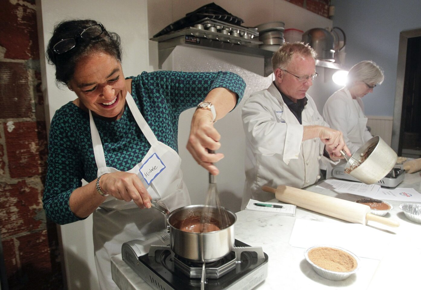 U-T San Diego dining and lifestyle reporter Michele Parente, left, heats up chocolate for chocolate cream pie as she and Nick and Nancy Benson take a pie baking class.