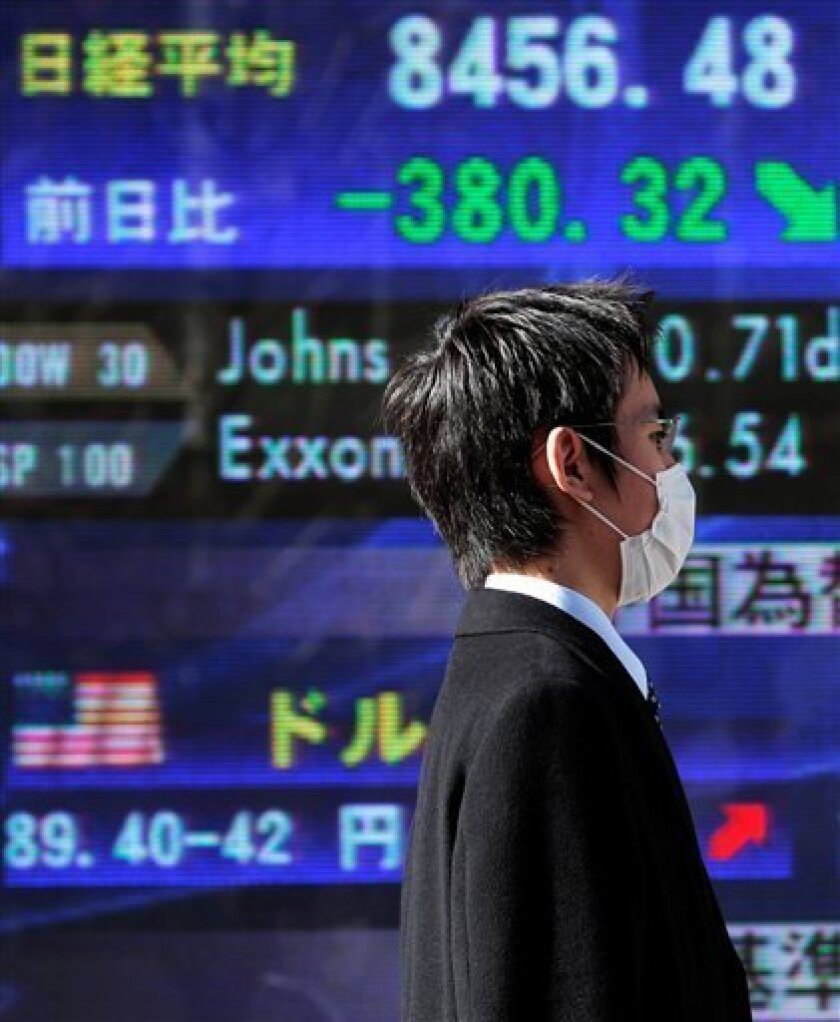 A businessman walks past an electronic stock board in Tokyo, Japan, Tuesday, Jan. 13, 2009. The benchmark Nikkei 225 average lost 380.32 points, or 4.30 percent in morning session. (AP Photo/Itsuo Inouye)
