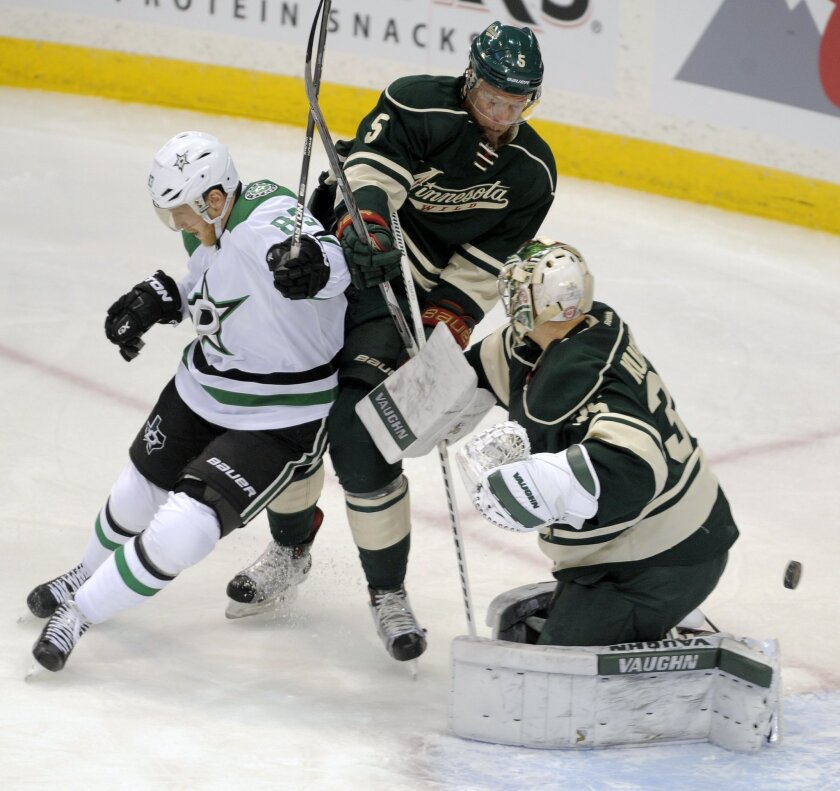 Minnesota Wild's Christian Folin (5) , of Sweden, forces Dallas Stars' Ales Hemsky, left, Czech Republic, away from the goal as the Stars' goalie Darcy Kuemper, right, make the save in the first period of an NHL hockey game, Tuesday, Feb. 9, 2016, in St. Paul, Minn. (AP Photo/Tom Olmscheid)
