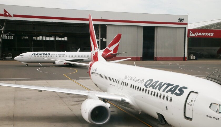 A Qantas plane maneuvers behind another parked at a gate at Sydney Airport in Sydney, Thursday, Feb. 26, 2015. Qantas Airways Ltd. has posted a 206 million Australian dollar ($162 million) profit for the first six months since it recorded a $2.6 billion loss for the year. (AP Photo/Rick Rycroft)