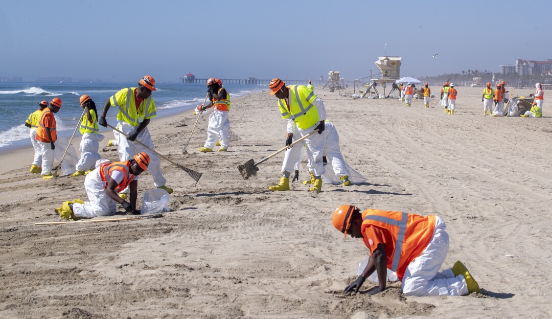 Crew members in yellow and orange vests rake and sift sand on the beach