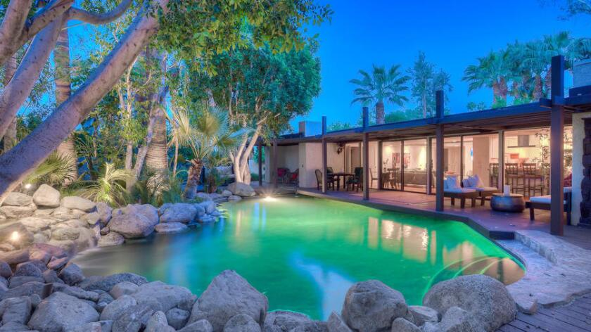 The gated contemporary-style home, built in 1955, sits amid lush landscaping on more than half an acre in Palm Desert.