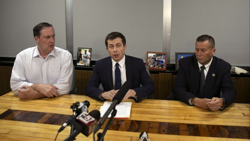 South Bend Mayor Pete Buttigieg, center, speaks during a news conference, Sunday, June 16, 2019, in