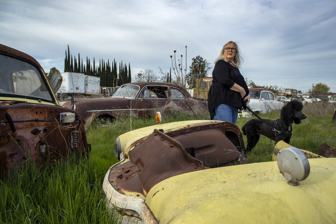 Georgia DeFilippo with her dog stands in a lot strewn with old cars, junk and antiques.