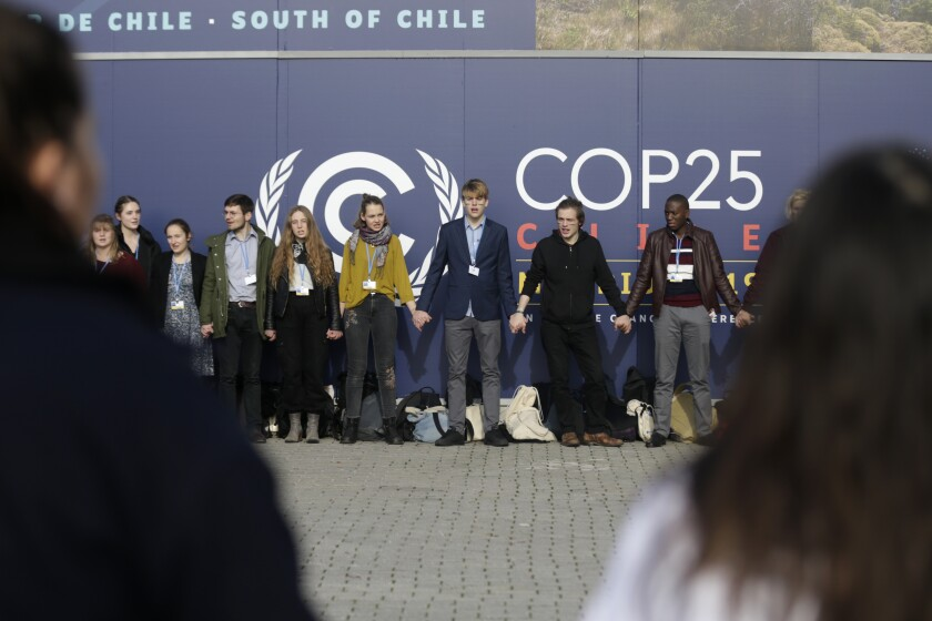 Young activists from the 'Fridays For Future' climate protest Movement form a human chain at the COP25 Climate summit in Madrid, Spain, Monday, Dec. 9, 2019. A global U.N.sponsored climate change conference is taking place in Madrid. (AP Photo/Andrea Comas)