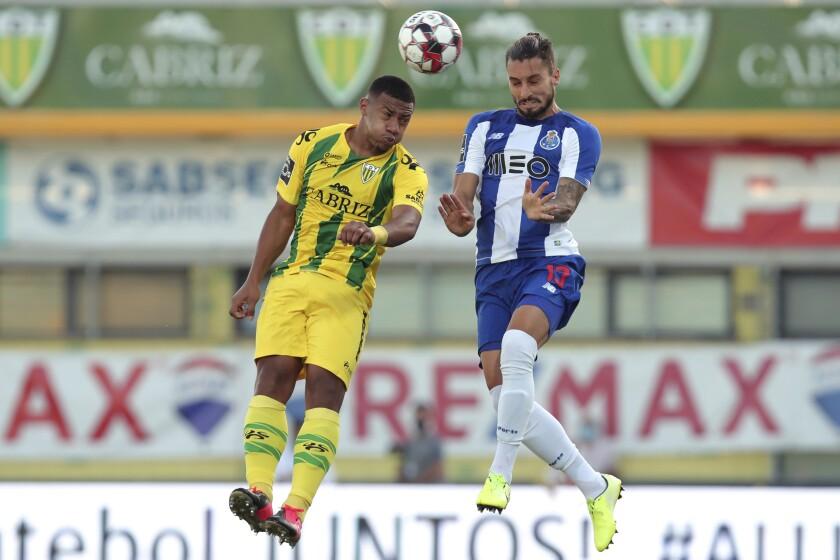 Porto's Alex Telles jumps for the ball against Tondela's Fahd Moufi during the Portuguese league soccer match between Tondela and FC Porto and Leipzig at the Joao Cardoso stadium in Tondela, Portugal, Thursday, July 9, 2020. The Portuguese league soccer matches are being played without spectators because of the coronavirus pandemic. (AP Photo/Luis Vieira)