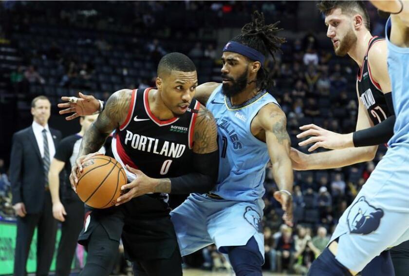 El jugador Mike Conley (c) de Memphis Grizzlies en acción ante Damian Lillard (i) de Portland Trail Blazers durante un partido. EFE/Archivo