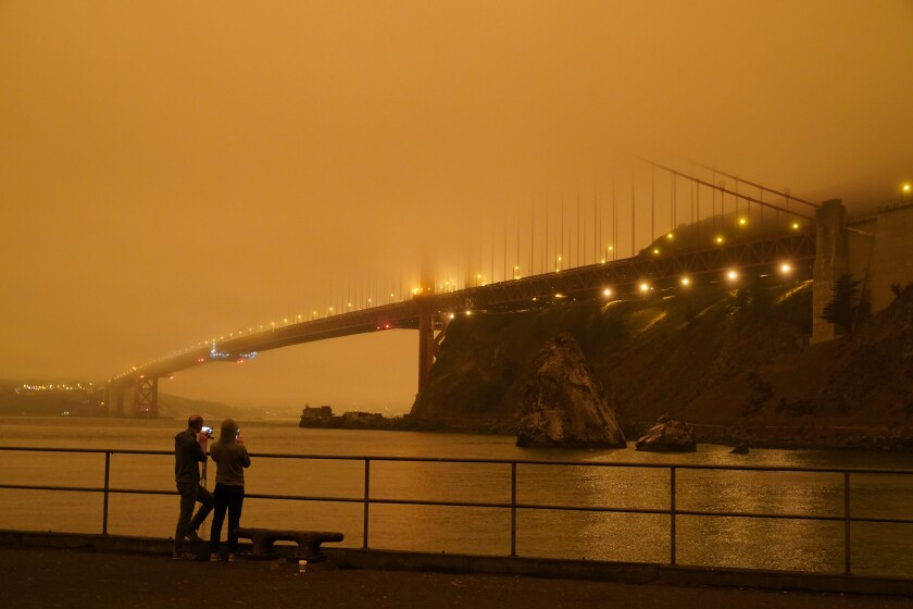 Patrick Kenefick, left, and Dana Williams, both of Mill Valley, Calif., record the darkened Golden Gate Bridge covered with smoke from wildfires Wednesday, Sept. 9, 2020, from a pier at Fort Baker near Sausalito, Calif. The photo was taken at 9:47 a.m. in the morning. (AP Photo/Eric Risberg)