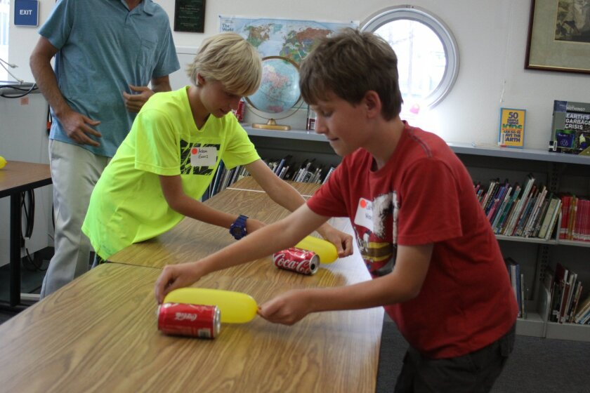 Adam Gans and Colton Moseley use static electricity to 'pull' soda cans.