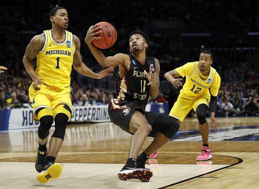 Florida State guard Braian Angola (11) shoots between Michigan guard Charles Matthews (1) and guard Muhammad-Ali Abdur-Rahkman (12) during the second half of an NCAA men's college basketball tournament regional final Saturday, March 24, 2018, in Los Angeles.