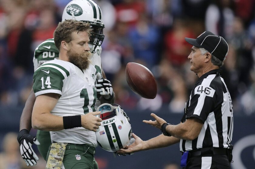New York Jets quarterback Ryan Fitzpatrick (14) trades official Perry Paganelli (46) the ball for his helmet after he scored a touchdown against the Houston Texans during the second half of an NFL football game, Sunday, Nov. 22, 2015, in Houston. Fitzpatrick lost his helmet on the play. (AP Photo/Patric Schneider)