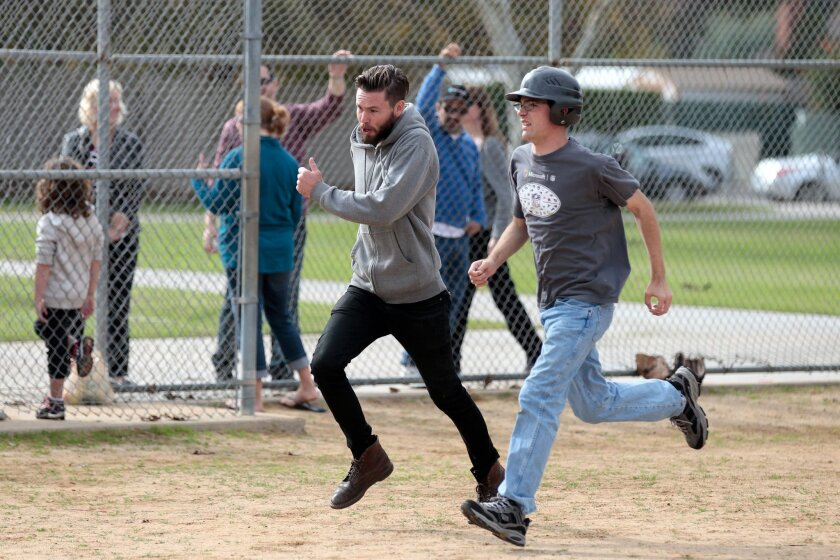 Autism Baseball League volunteer Kyle Murray, left, escorts Chase Ryniker, 18, to first base during an adapted baseball game in Rancho Penasquitos on Saturday.