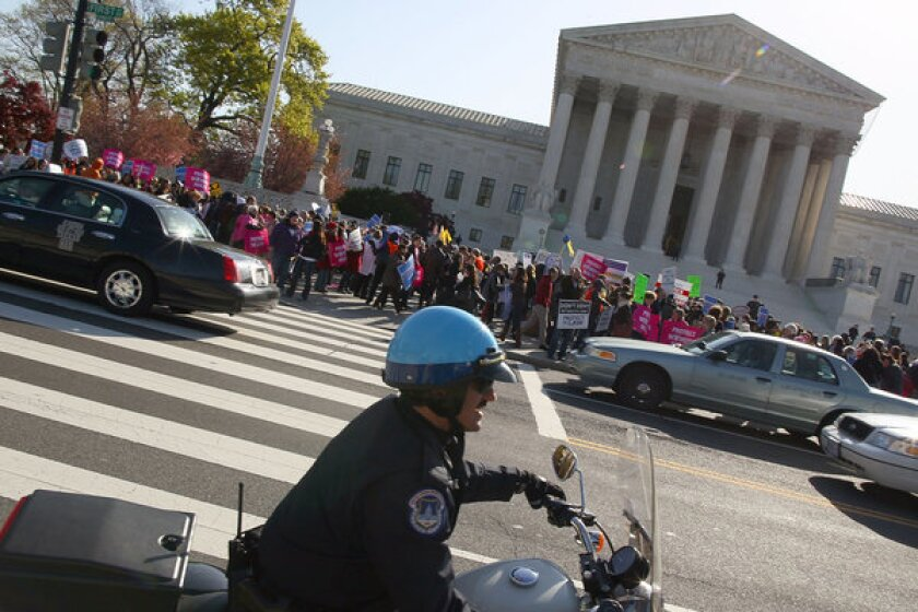 Supporters and opponents of the healthcare law demonstrate outside the Supreme Court.