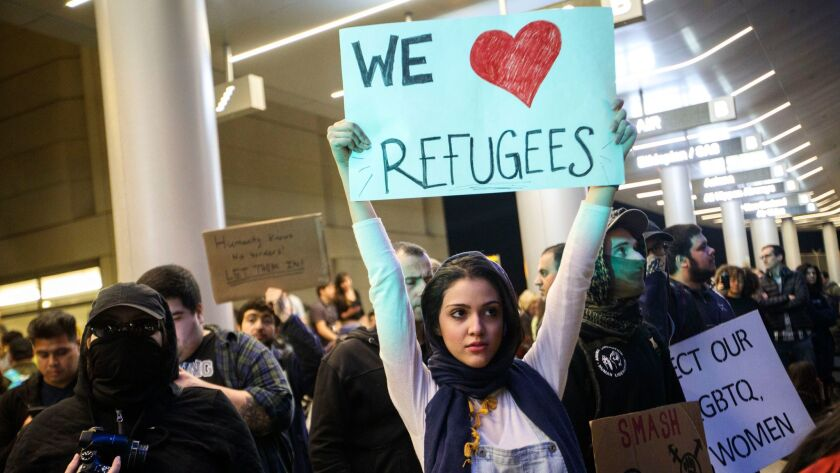 """A woman holds a """"We Heart Refugees"""" sign as people protest in front of the Tom Bradley International"""