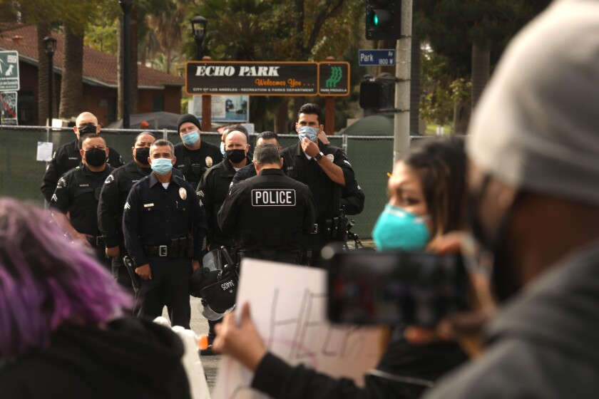 Police and protesters stand outside a fenced Echo Park