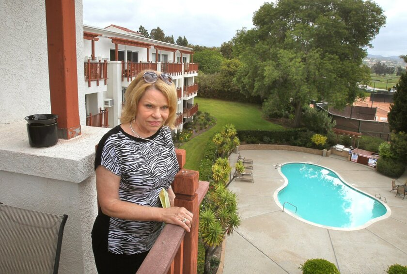 Real estate broker/property manager Roberta Murphy stands on the balcony of an upper floor, one-bedroom condo for sale in May at the La Costa Resort and Spa. Many of the units in the building have been short-term vacation rentals since the building was constructed in 1972.
