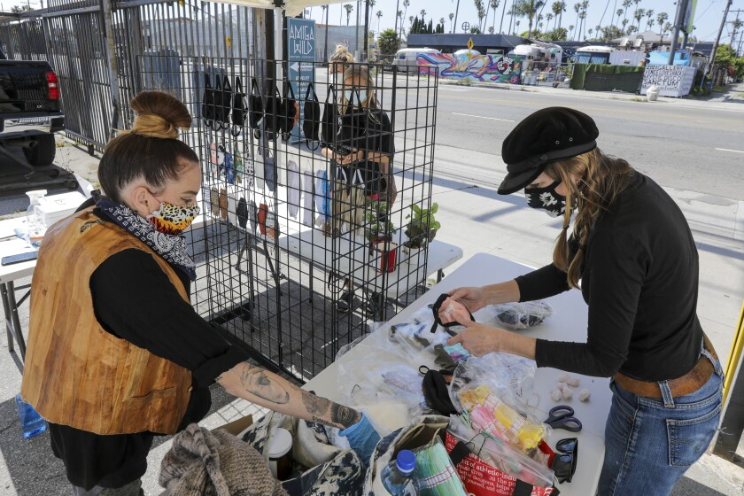 Sadie Gilliam, left, and Alisun Franson sell face masks from a stand in front of their store in Venice.