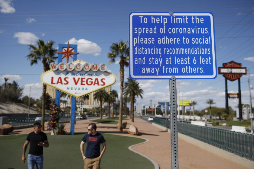 """""""Welcome to Fabulous Las Vegas Nevada"""" sign is paired with a sign about social distancing in the time of coronavirus."""