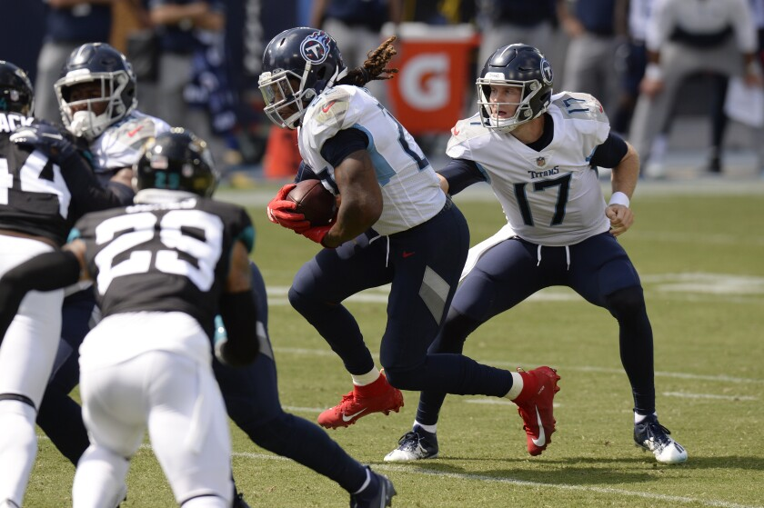Tennessee Titans quarterback Ryan Tannehill (17) hands off to running back Derrick Henry in the first half of an NFL football game against the Jacksonville Jaguars Sunday, Sept. 20, 2020, in Nashville, Tenn. (AP Photo/Mark Zaleski)