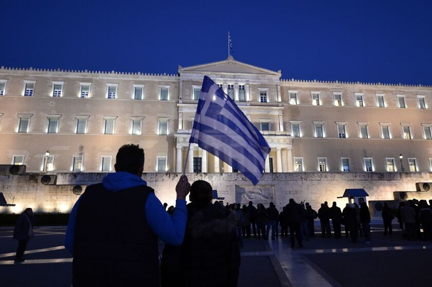 A man holds a Greek flag in front of the Parliament building in Athens at a rally in support of the new government on Feb. 20.