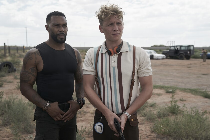 """Omari Hardwick and Matthias Schweighöfer stand pensively in the desert in the movie """"Army of the Dead."""""""