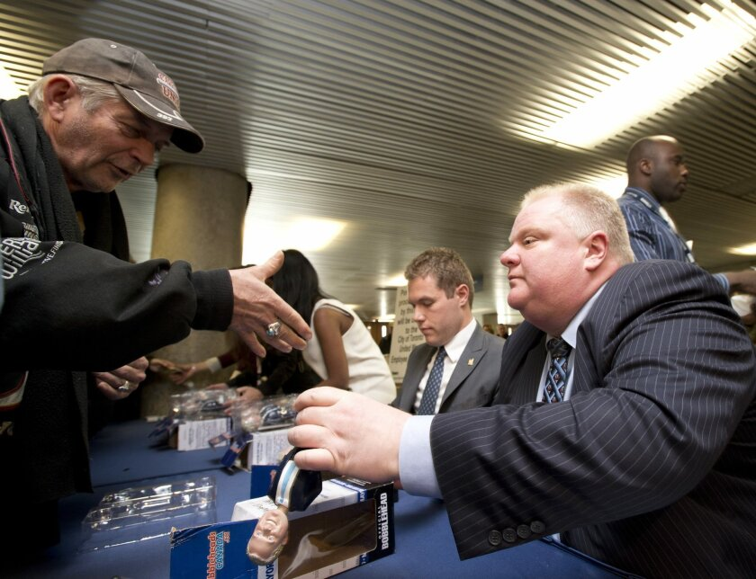 Toronto Mayor Rob Ford, right, autographs a bobblehead doll in his likeness Tuesday, Nov. 12, 2013, at city hall in Toronto. Hundreds of people lined up to be the first to own the bobblehead doll. The defiant mayor declared on Monday, Nov. 11, that he intends to stay in office despite pressure to s