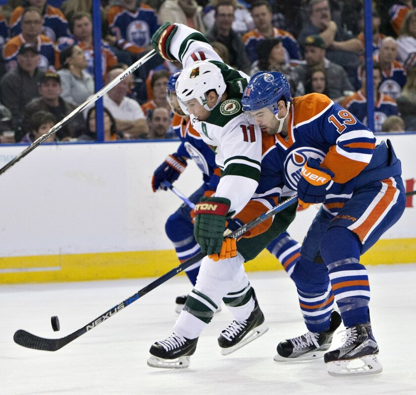 Minnesota Wild's Zach Parise (11) and Edmonton Oilers' Justin Schultz (19) vie for the puck during the first period of an NHL hockey game Thursday, Feb. 18, 2016, in Edmonton, Alberta. (Jason Franson/The Canadian Press via AP)