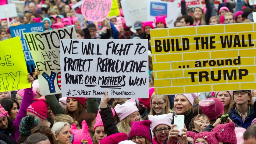 Protesters with bright pink hats and signs begin to gather early on Jan. 21, the first full day of Donald Trump's presidency, in Washington, D.C.