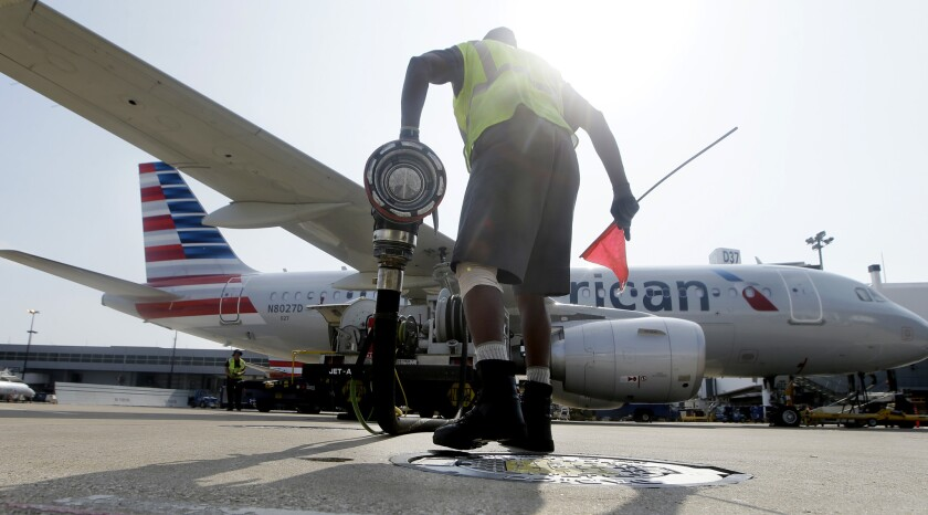 In this Thursday, Aug. 26, 2015 photo, Scott Mills finishes fueling up an American Airlines jet at D