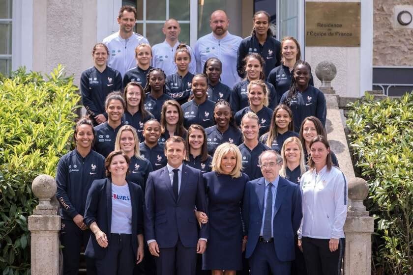 French Sports Minister Roxana Maracineanu, President Emmanuel Macron, First Lady Brigitte Macron, French Football Federation president Noel Le Graet and national team coach Corinne Diacre stand in front of players and staff members June 4 at Clairefontaine.