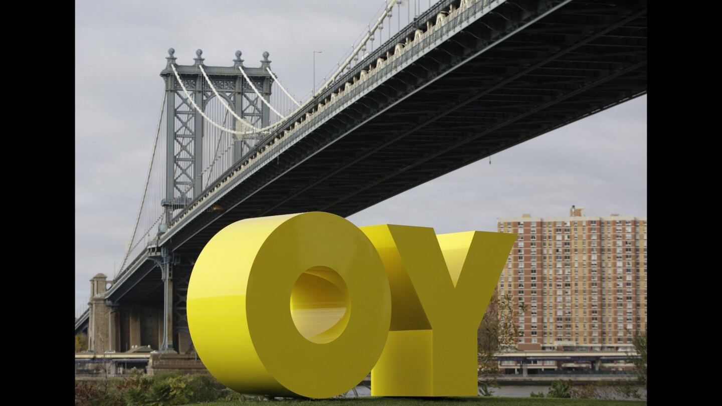 """The Manhattan Bridge frames a bright yellow monumental sculpture by artist Deborah Kass in Brooklyn Bridge Park, on Wednesday, Nov. 11, 2015, in New York. When viewed from Manhattan, the sculpture reads """"Yo,"""" but when viewed from Brooklyn it spells the popular Yiddish expression """"Oy."""" The aluminum sculpture was commissioned by Brooklyn developer Two Trees Management Company and will remain up until August 2016."""