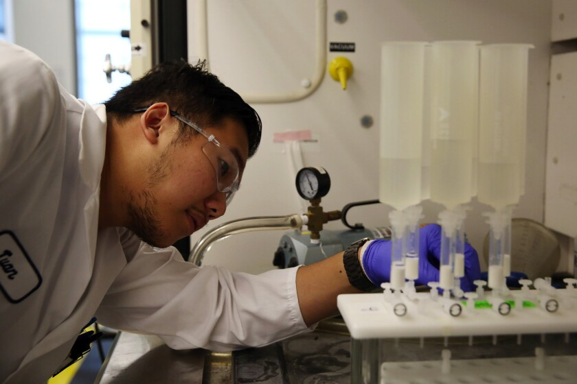 Twan Nguyen examines a machine testing water for chemicals at the Orange County Water District.
