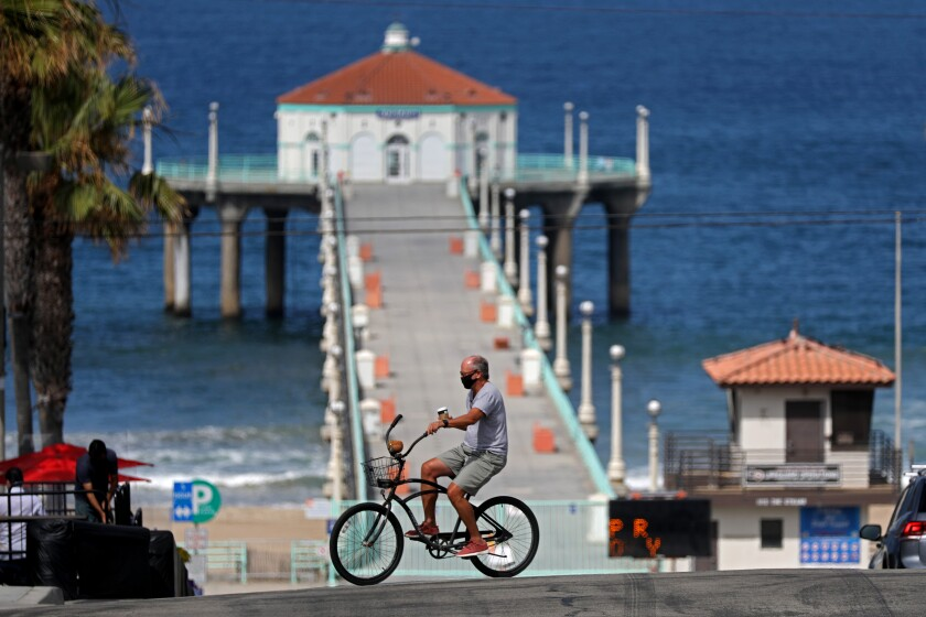 A bicyclist rides near the closed pier in Manhattan Beach on Friday, July 3, 2020.