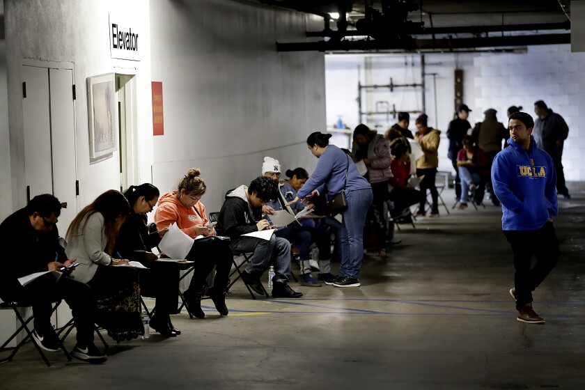 Unionized hospitality workers wait to apply for unemployment benefits at the Hospitality Training Academy in Los Angeles.