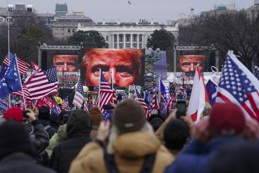 Trump supporters hold flags and banners while three big screens show the top half of Trump's face.