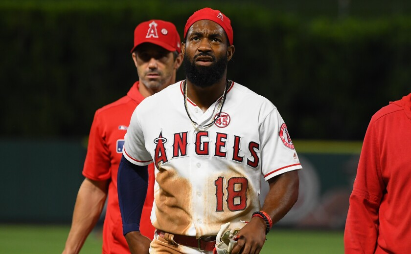 Angels Brian Goodwin is helped off the field after he injured his back diving into second base for a double in the second inning against the Houston Astros at Angel Stadium on Thursday.