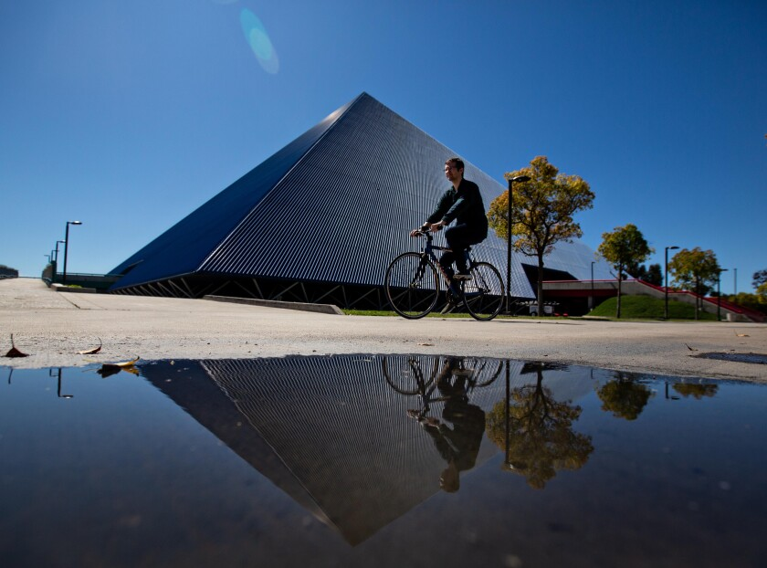 A cyclist is seen in front of a pyramid-shaped structure.