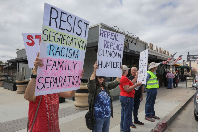 Anti-Congressman Duncan Hunter protesters hold signs in front of the  Ramona Mainstage theater on Main Street prior to the town hall meeting with Hunter and his father, retired Congressman Duncan Hunter.