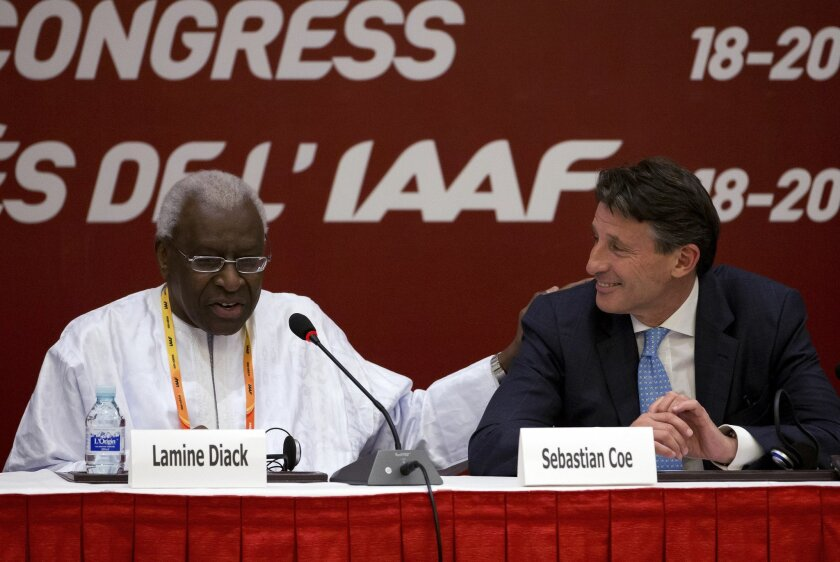 FILE - In this Aug.19, 2015 file photo, International Association of Athletics Federations outgoing president Lamine Diack, left, speaks next to newly elected president Sebastian Coe during a press briefing at the IAAF Congress at the National Convention Center in Beijing. The French office that ha