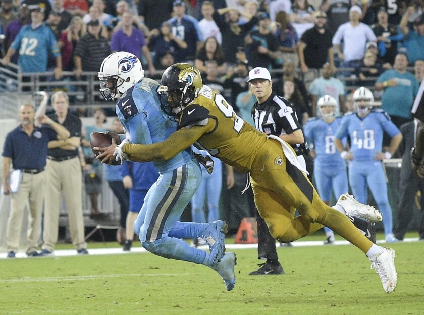 Jacksonville Jaguars defensive end Andre Branch, right, sacks Tennessee Titans quarterback Marcus Mariota on the final play of an NFL football game in Jacksonville, Fla., Thursday, Nov. 19, 2015. Jacksonville won 19-13. (AP Photo/Phelan M. Ebenhack)