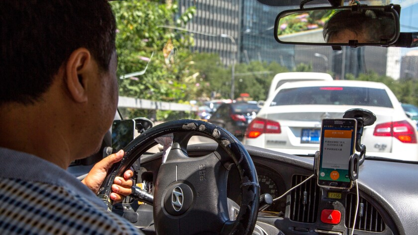 A taxi driver uses the Didi Dacha app.