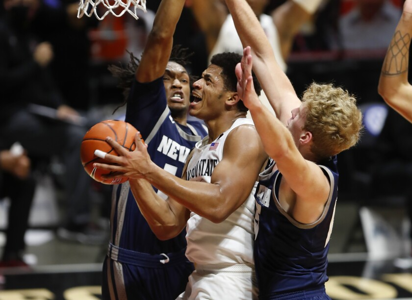 SDSU's Matt Mitchell is fouled by Nevada's Tre Coleman (left) in the first game against Nevada on Thursday.