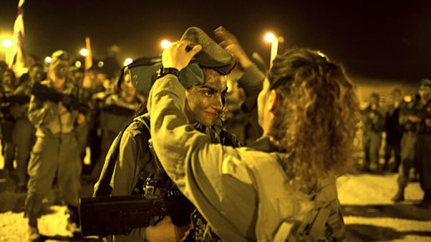 An Israeli female soldier receives her graduation cap after a march in the Negev desert this month.