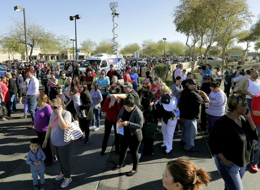 Parents wait to reunite with their children, Friday, Feb. 12, 2016, in Glendale, Ariz., after two students were shot and killed at Independence High School in the Phoenix suburb. The danger at the campus was over, police said, as worried parents crowded stores nearby to await word on their children
