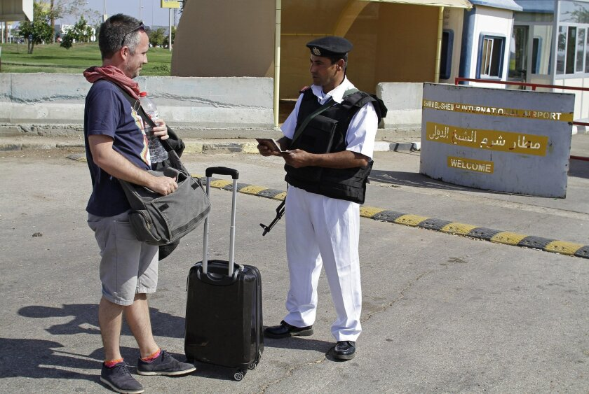 An Egyptian policeman checks a Russian tourist's passport at the main entrance to the Sharm el-Sheikh airport in Egypt on Saturday, Nov. 7, 2015. Egypt's Foreign Minister Sameh Shoukry complained on Saturday that Western governments had not sufficiently helped Egypt in its war on terrorism and had
