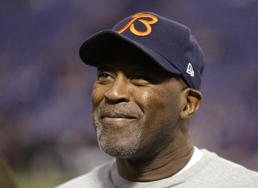 In this Dec. 9, 2012, photo, Chicago Bears coach Lovie Smith smiles before the Bears' NFL football game against the Minnesota Vikings in Minneapolis. A person familiar with the negotiations says former Bears coach Smith has reached an agreement to coach the Tampa Bay Buccaneers. Speaking to The Associated Press on Wednesday night, Jan. 1, 2014, on the condition of anonymity because an official announcement hasn't been made, the person also says former Minnesota Vikings coach Leslie Frazier will be the Buccaneers' defensive coordinator. (AP Photo/Charlie Neibergall)