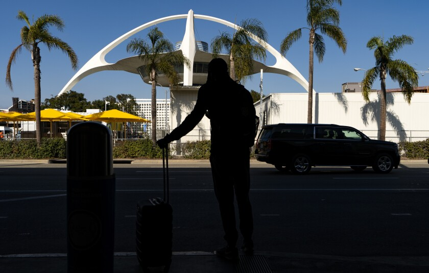 A travelers awaits for transportation at the Los Angeles International Airport in Los Angeles Wednesday, Nov. 25, 2020. Residents were urged to avoid nonessential travel during what is typically the busiest travel period of the year. Anyone entering California was advised to quarantine for two weeks. (AP Photo/Damian Dovarganes)