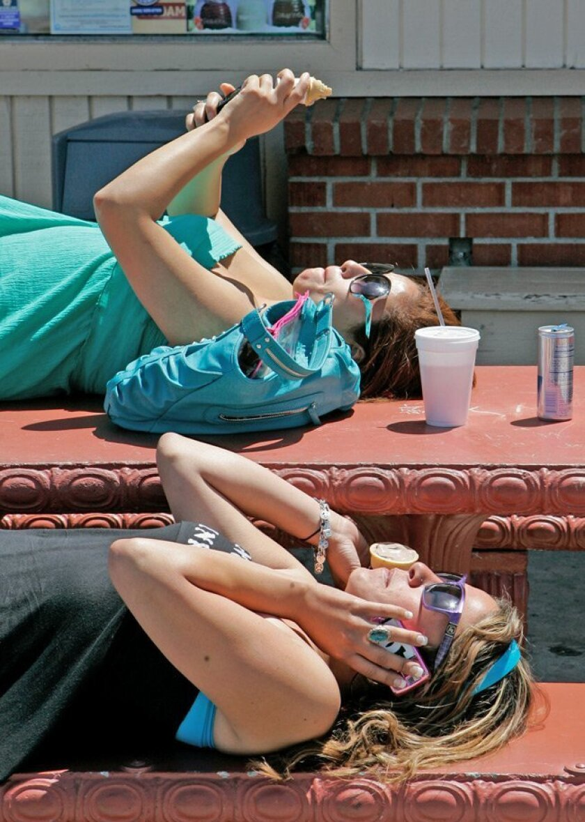 Courtney Tabro (on cell phone), 23, and friend Valerie Star, 26, of San Marcos stretch out in the sun Thursday outside Cessy Taco Shop in Carlsbad.
