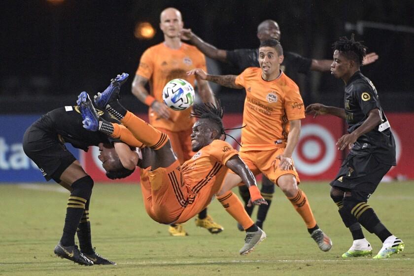 Houston Dynamo forward Alberth Elis falls over LAFC midfielder Eduard Atuesta while fighting for a header in Kissimmee, Fla.