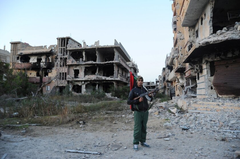In this picture taken Tuesday, Feb. 23, 2016, a civilian fighter, holding the Libyan flag, stands in front of damaged buildings in Benghazi, Libya. Army units, backed by civilian fighters, cleared a major part of the eastern city of Islamic extremists Tuesday, following nearly two years of deadly fighting. (AP Photo/Mohammed el-Shaiky)
